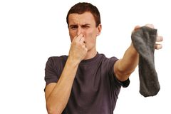 The guy with dirty socks in his hands on a white background. stock image
