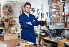 Guy displaying his workplace and tools at workshop. Glad  positive guy displaying his workplace and tools at workshop Royalty Free Stock Images