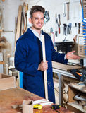 Guy displaying his workplace and tools at workshop. Smiling cheerful positive guy displaying his workplace and tools at workshop Royalty Free Stock Photos