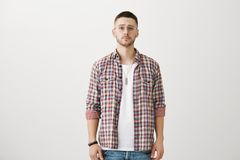 Guy do not believe you. Portrait of attractive slender unshaved man in trendy eyewear standing in stylish outfit over. Gray background, lifting eyebrow while Royalty Free Stock Photography