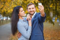 A guy does selfie with a girl against the backdrop of an autumn park royalty free stock photos