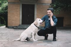A guy with a dog. A moment that was captured in a beautiful day. A guy is squatting near the golden labrador retreiver at the backyard. He is talking on the Stock Images