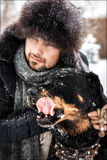 The guy with the dog in the park in winter. Snowing.  Stock Photography
