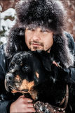The guy with the dog in the park in winter. Snowing.  Royalty Free Stock Photography