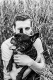 Guy with a dog for a walk, a French bulldog in the hands of a man. Blond guy with a dog for a walk, a French bulldog in the hands of a man Stock Photos