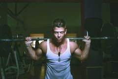 Guy doing exercises with barbell Royalty Free Stock Photos
