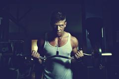 Guy doing exercises with barbell Stock Photography