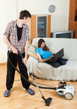 Guy doing house cleaning during girl resting Royalty Free Stock Photos