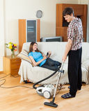 Guy doing house cleaning during girl resting over sofa Royalty Free Stock Photography