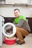 Guy  doing laundry with washing machine Stock Image