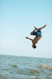 Guy doing a somersault on sea background Stock Photo