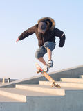 Guy doing a stunt with his skateboard. Young teenage guy doing a stunt with his skate board Royalty Free Stock Photography