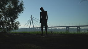 Guy doing workout at the open air. Silhouette of a man performing exercise outdoors. In the background the bridge behind him ride vehicle. Gyu warming up neck stock video