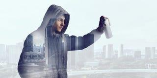 Guy drawing with spray . Mixed media . Mixed media Royalty Free Stock Photo