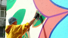 Guy drawing with spray on wall in city park. Close-up stock video