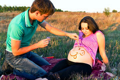 Guy draws a face on a stomach of pregnant woman Stock Photos
