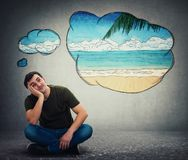 Guy dreamer imagining a exotic seaside beach adventure. Young man dreamer sitting on the floor holding hand under cheek leaning on a side looking up dreaming of stock photo