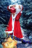 Santa Claus in winter forest. A guy dressed as Santa Claus stands in the forest among the trees and holding a box of gifts royalty free stock images