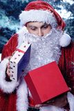 Santa Claus in a winter forest. Christmas and new year holiday. A guy dressed as Santa Claus in a winter forest opens gift box royalty free stock images