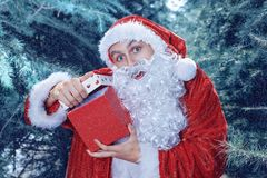Santa Claus in a winter forest. Christmas and new year holiday. A guy dressed as Santa Claus in a winter forest opens gift box stock photos