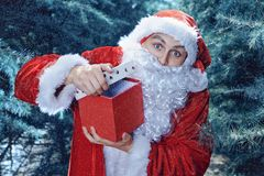 Santa Claus in a winter forest. Christmas and new year holiday. A guy dressed as Santa Claus in a winter forest opens gift box stock photo