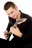 Guy dressed in black clothes sits and plays the guitar Royalty Free Stock Photo