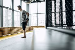 Guy dressed in the grey t-shirt  stretches his arms in the boxing gym with panoramic windows royalty free stock photography
