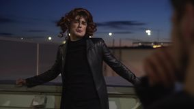 Guy dressed like woman with make-up,wearing black clothes and wig, sings outside stock video