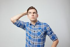 A guy dressed in a plaid shirt puts hand on the head on a white background in the studio stock photography