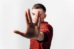 The guy dressed in red checkered shirt and jeans stands with his hand in front of him on the white background in the. Studio royalty free stock photo