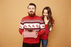 Guy dressed in red and white sweater with deer holds a Christmas present in his hands and a girl looks out from behind stock photo