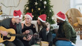 A guy dressed in Santa Clause`s hat plays a guitar around near Christmas tree. Friends celebrate Christmas in the loft