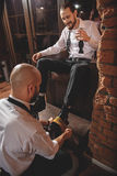 Guy drinking beverage and looking on shoeshiner Royalty Free Stock Photography