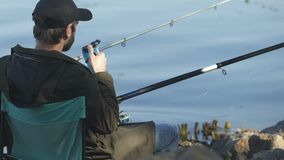 Guy drinking beverage from thermo cup, holding fishing rod, angling activity. Stock footage stock video footage