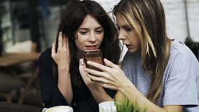 Guy is drinking coffee while his girlfriends are on their social media in a cafe. Close up of a guy s hand with a large cup of coffee. His two female friends are stock footage