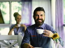 Guy drinks coffee or tea at table. Morning coffee time concept. Man with beard and happy face. Holds cup of hot drink on light blue cafe background. Romantic stock images