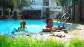 Guy drinks water girl laughs and swims across pool stock video footage