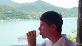 The guy drinks water on a hot day. Panoramic view of the sea and mountains stock video