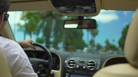Guy driving expensive car down road with palm trees, business driver, service. Stock footage stock video footage
