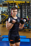 A guy with dumbbells is doing sports in the gym Stock Photos