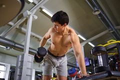 A guy with dumbbells is doing sports in the gym Stock Photo