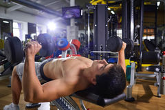 A guy with dumbbells lying doing exercises in the gym.  Stock Photo