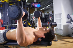 A guy with dumbbells lying doing exercises in the gym.  Stock Photos
