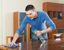 Guy dusting wooden table with rag and cleanser at home. Smiling guy dusting wooden table with rag and cleanser at home Stock Photos