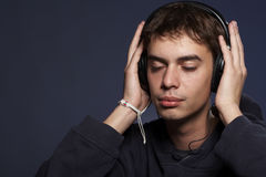 The guy in ear-phones. Portrait of the guy listening to music in ear-phones stock photography