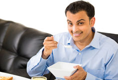 Guy eating breakfast indoors Stock Images