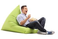 Guy eating popcorn and watching something Stock Photos