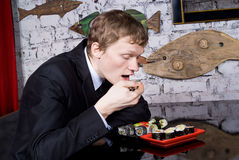 Guy eats sushi in a restaurant Royalty Free Stock Photo