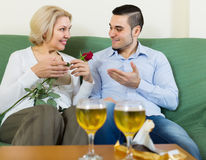 Guy and elderly woman drinking wine and smiling royalty free stock photography