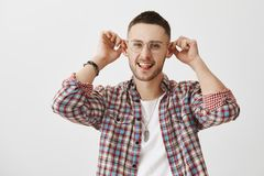 Guy with elf ears thinks they add charm to appearance. Portrait of good-looking funny man in eyeglasses holding ears Royalty Free Stock Photos